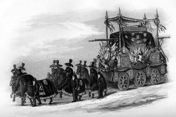 An elaborate hearse pulled by 12 black horses